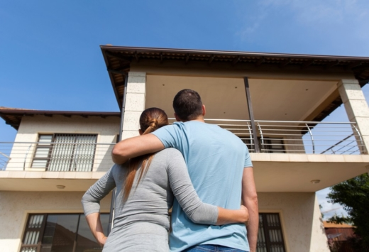 Young couple looking up at newly purchased home